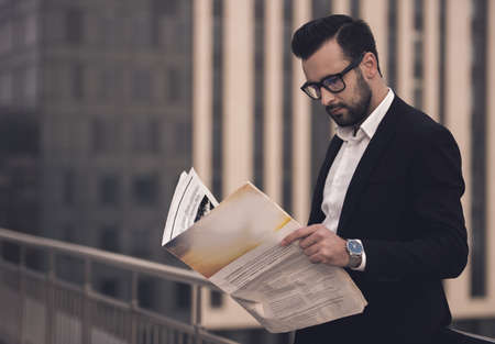 Handsome businessman in suit and glasses is reading newspaper while standing on the balcony