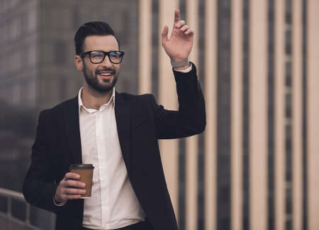 Handsome businessman in suit and glasses is holding a cup of coffee, waving and smiling while standing on the balcony