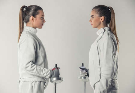 Beautiful female fencers in protective clothing are holding weapon and looking at each other, on gray background, side view Stock Photo