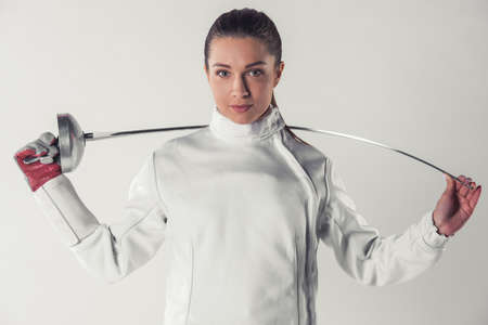 Beautiful female fencer in protective clothing is holding a weapon and looking at camera, on gray background