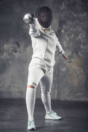 Female fencer in protective clothing is using weapon while practicing on dark gray background Stok Fotoğraf
