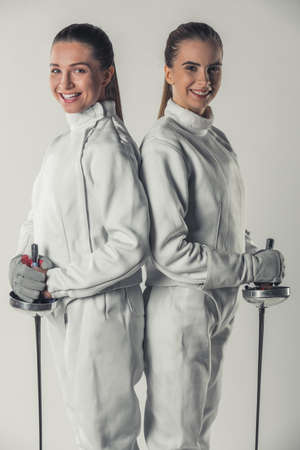 Beautiful female fencers in protective clothing are holding weapon, looking at camera and smiling, on gray background