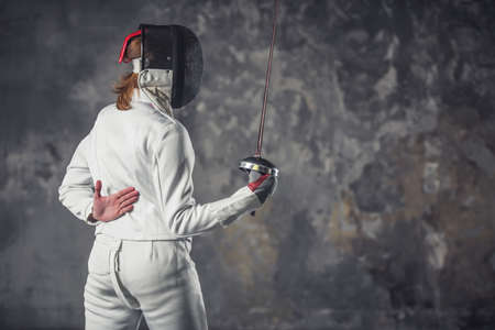 Female fencer in protective clothing is using weapon while practicing on dark gray background Stock Photo