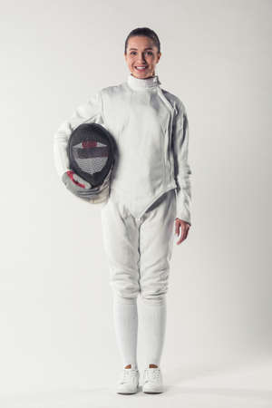 Beautiful female fencer in protective clothing is holding a mask, looking at camera and smiling, on gray background, full-length