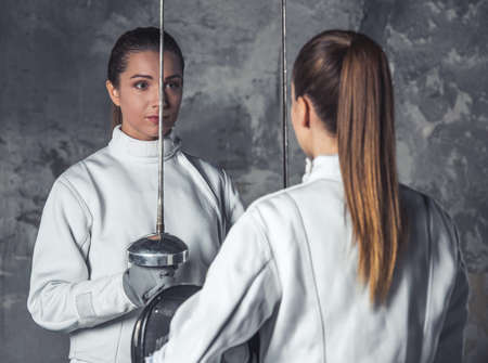 Beautiful female fencers in protective clothing are holding masks and weapon and looking at each other, on dark gray background Stock Photo