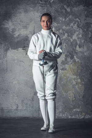 Beautiful female fencer in protective clothing is holding a weapon, looking at camera and smiling, on dark gray background, full-length Stok Fotoğraf