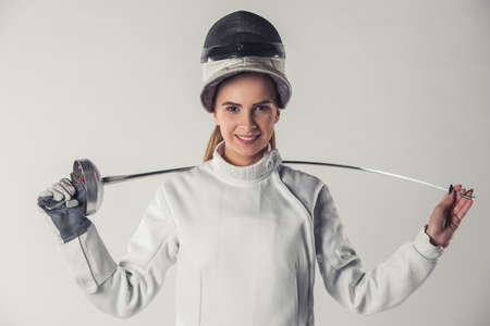Attractive female fencer in protective clothing is holding a weapon, looking at camera and smiling, on gray background