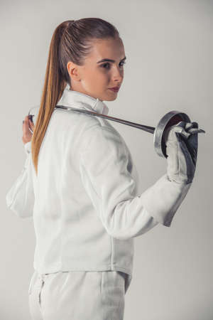 Attractive female fencer in protective clothing is holding a weapon, on gray background