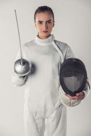 Attractive female fencer in protective clothing is holding a mask and a weapon and looking at camera, on gray background