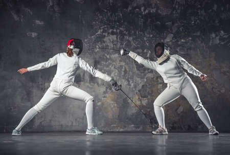 Female fencers in protective clothing are fighting on dark gray background, full-length Stok Fotoğraf - 96751124