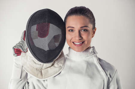 Beautiful female fencer in protective clothing is holding a mask, looking at camera and smiling, on gray background