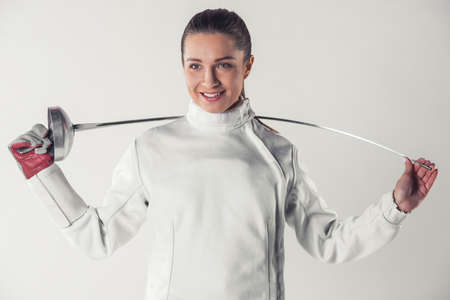 Beautiful female fencer in protective clothing is holding a weapon and smiling, on gray background