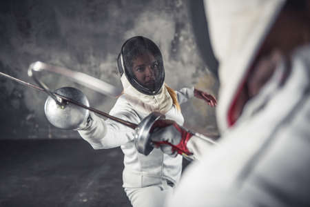 Female fencers in protective clothing are fighting on dark gray background Foto de archivo - 96751132