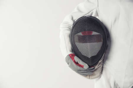 Cropped image of female fencer in protective clothing holding a mask, on gray background