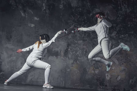 Female fencers in protective clothing are fighting on dark gray background, full-length