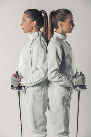 Beautiful female fencers in protective clothing are holding weapon while standing back to back on gray background, side view