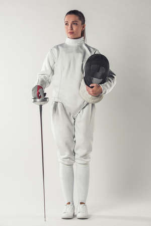 Beautiful female fencer in protective clothing is holding a mask and a weapon, on gray background, full-length