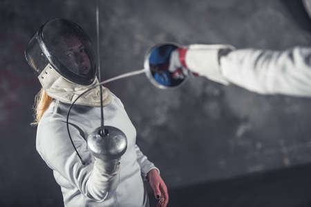 Female fencers in protective clothing are fighting on dark gray background