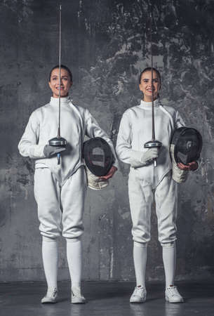 Beautiful female fencers in protective clothing are holding masks and weapon and smiling, on dark gray background, full-length Stock Photo