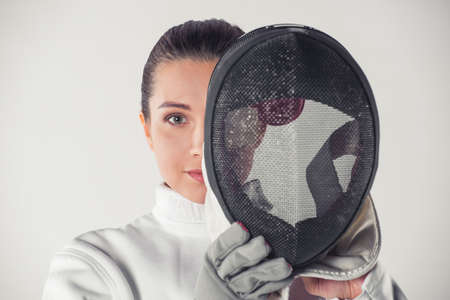 Beautiful female fencer in protective clothing is holding a mask and looking at camera, on gray background