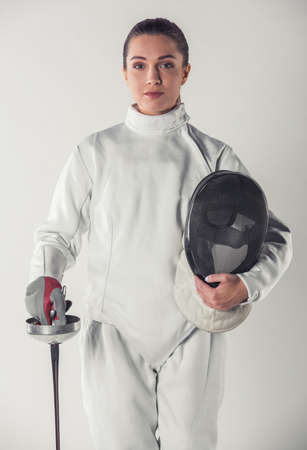 Beautiful female fencer in protective clothing is holding a mask and a weapon and looking at camera, on gray background