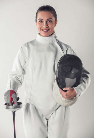 Beautiful female fencer in protective clothing is holding a mask and a weapon, looking at camera and smiling, on gray background Stok Fotoğraf