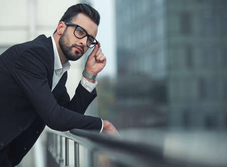 Handsome businessman in suit and glasses is looking away and thinking while leaning on the balcony