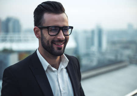 Handsome businessman in suit and glasses is smiling while standing on the balcony