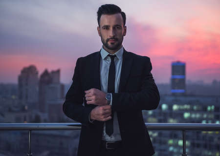 Handsome businessman in suit is adjusting his cufflinks while standing on the balcony, beautiful sunset behind him