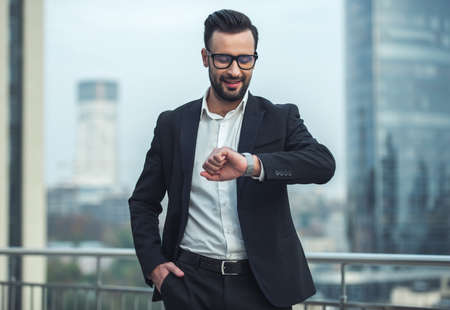Handsome businessman in suit and glasses is looking at his watch and smiling while standing on the balcony