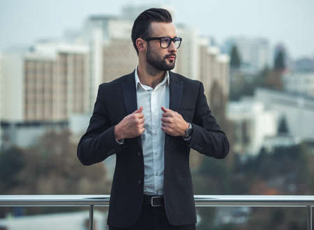 Handsome businessman in suit and glasses is looking away while standing on the balcony Stock Photo