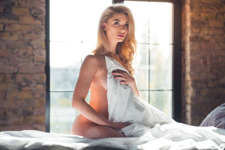 Naked blonde woman is covering her body with a blanket and looking sensually at camera while sitting on bed