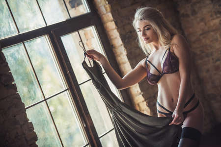 Sexy blonde woman in lingerie and stockings is holding a dress while standing near the window