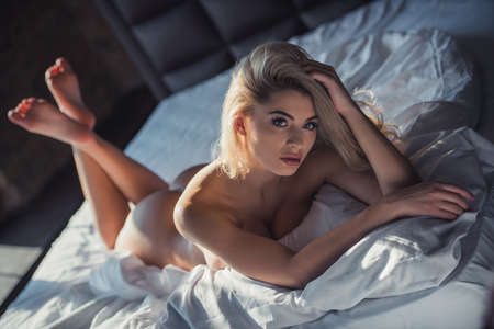 Naked blonde woman is looking at camera while lying on bed, sunshine on her body 스톡 콘텐츠