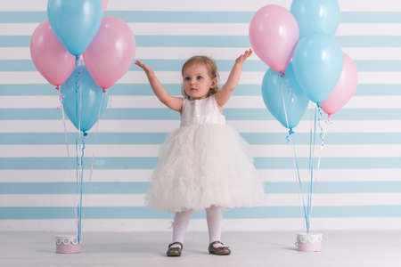 Cute little girl in fluffy white dress is raising hands up while standing near balloons, on light background