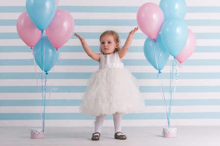 Nettes kleines Mädchen im flaumigen weißen Kleid hebt Hände oben bei der Stellung von nahen Ballonen, auf hellem Hintergrund an Standard-Bild - 97761002