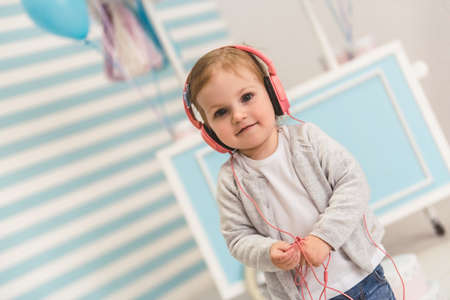 Cute little girl in headphones is looking at camera and smiling while listening to music in the children's room Banque d'images - 97761005