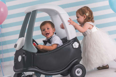 Cute kids in elegant clothes on light background. Boy is sitting in the toy car, girl is pushing him