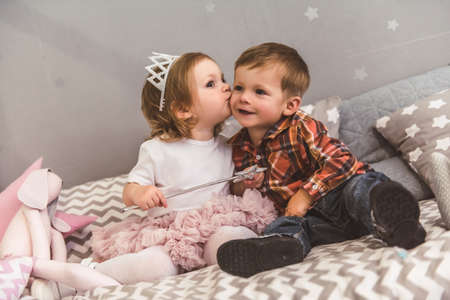 Cute kids are playing together in the childrens room. Boy is smiling while girl is kissing him in cheek