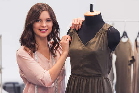 Beautiful fashion designer is standing near a dress model, looking at camera and smiling while working in her office