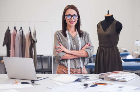 Attraktiver Modedesigner betrachtet Kamera und lächelt beim Stehen mit gekreuzten Armen in ihrem Büro Standard-Bild