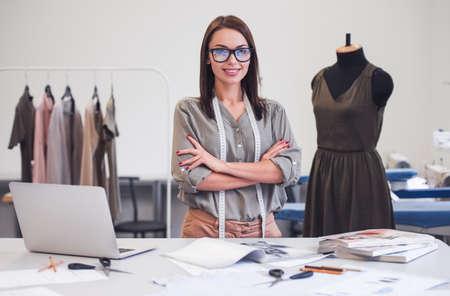 diseñador de moda atractivo está mirando la cámara y sonriendo mientras está de pie con los brazos cruzados en su oficina Foto de archivo