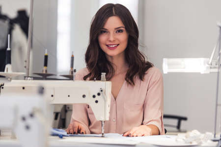 Beautiful dressmaker is using a sewing machine, looking at camera and smiling while working in tailor's workshop