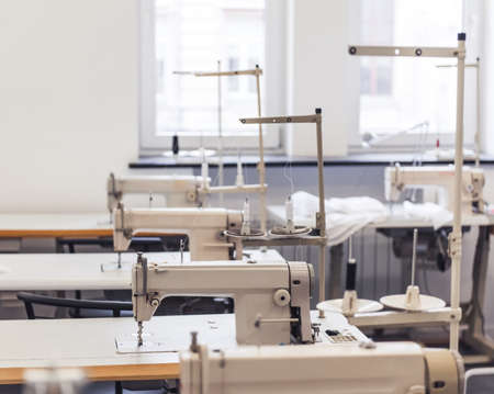 Clothes factory inside. Workplaces with modern sewing machines