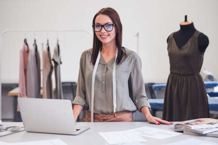 Attractive fashion designer is looking at camera and smiling while working in her office
