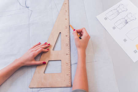 Cropped image of attractive fashion designer drawing sketch while working in her office Archivio Fotografico