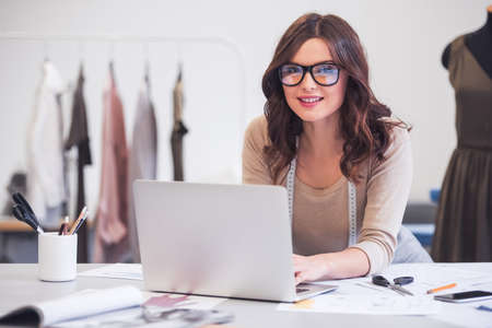 Beautiful fashion designer is using a laptop and smiling while working in her office Stock Photo