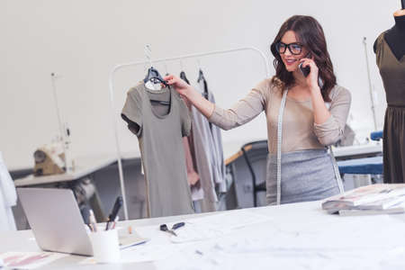 Beautiful fashion designer is holding a dress model, talking on the mobile phone and smiling while working in her office Stock Photo