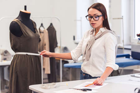 Attractive fashion designer is taking measurements of a dress model while working in her office Standard-Bild