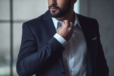 Cropped image of handsome confident man in suit touching collar